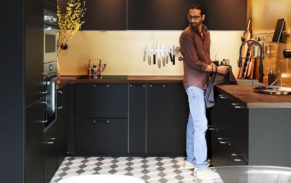 Muž stojí v kuchyni do U vybavené černými skříňkami. Na podlaze jsou černo-bílé dlaždice.