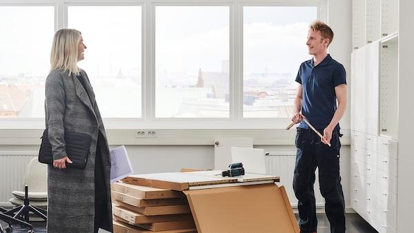 Muž stojí vedľa škatúľ s metrom v ruke, okolo sú biele steny a okno v pozadí.