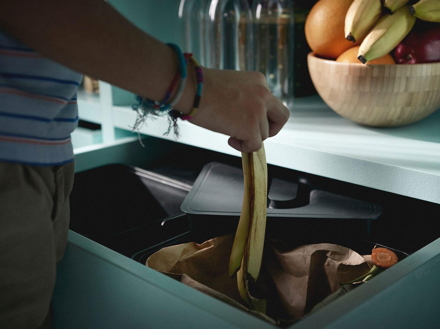 Muž vyhadzuje banánovú šupu do košov na triedenie odpadu VARIERA.
