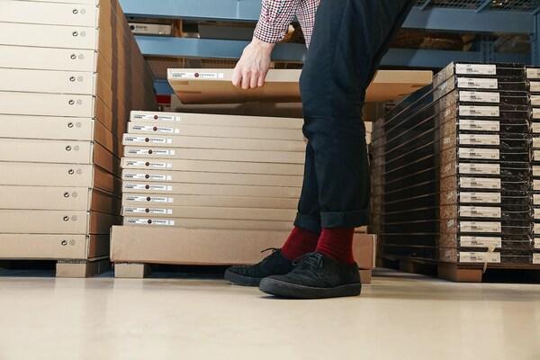 Muž zvedá zabalený výrobek v obchodním domě IKEA.