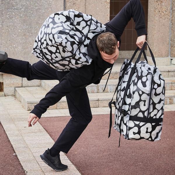 Мужчина несет на плечах и в руке черные сумки ОМБЮТЕ с прозрачными вставками и пытается танцевать.