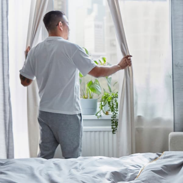 Мужчина придерживает занавески и смотрит в окно, на подоконнике стоит множество кашпо с зелеными растениями.
