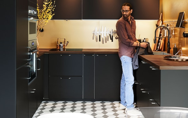 Мужчина стоит на современной, очень чистой, П-образной кухне в темных тонах. Клетчатый пол из керамической плитки, приглушенное освещение.