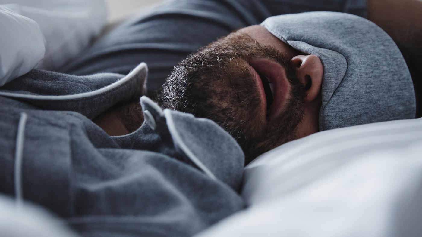 Мужчина в серой пижаме и такой же маске для сна спит с открытым ртом в кровати с постельным бельем НАТТЭСМИН.