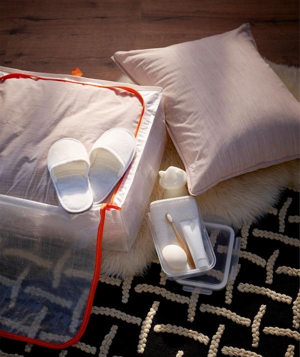 موضوعة على الأرض، علبة تخزين نصف معبأة بداخلها مفارش سرير، وشبشب، وفرشاة ومعجون أسنان، وصابون ومنشفة وضوء ليلي.