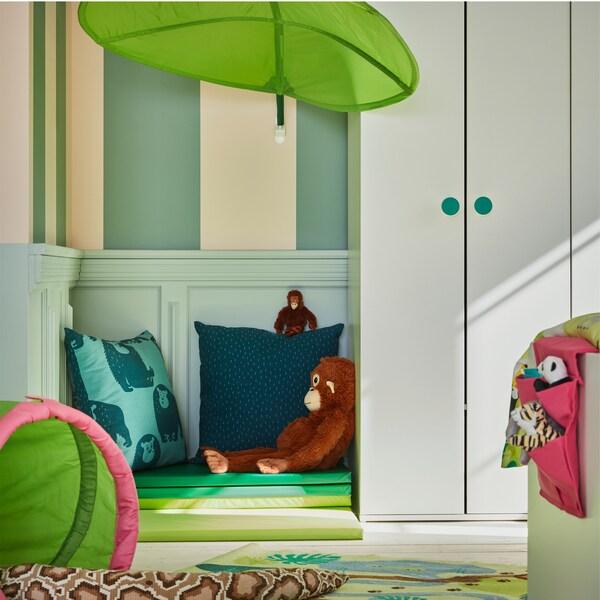 مظلة على شكل ورقة شجر خضراء مثبتة على الحائط، ودولاب ملابس أبيض وسجادة صالة ألعاب خضراء مطوية على الأرض.