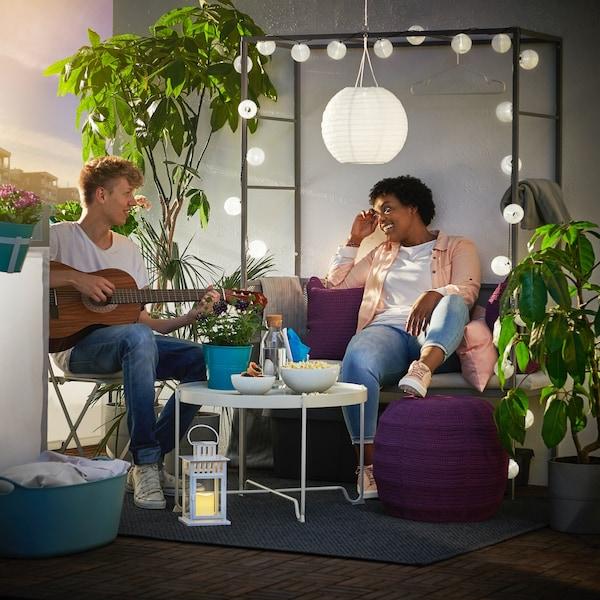 Na balkonie ławki z pergolą SVANÖ wiszą zasilane energią słoneczną lampy SOLVINDEN. Ławka jest udekorowana girlandą. Dziewczyna siedzi na ławce a chłopak gra na gitarze.