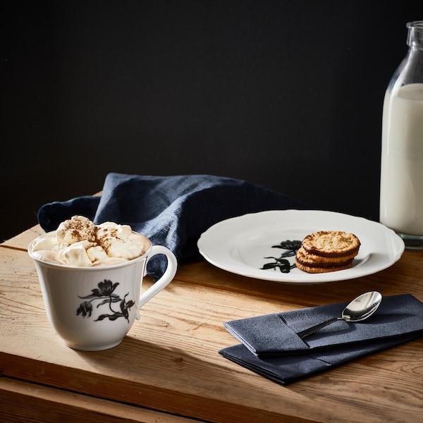 Na dřevěném stole stojí hrnek s kakaem a talířek se sušenkami, vzadu je lahev mléka.