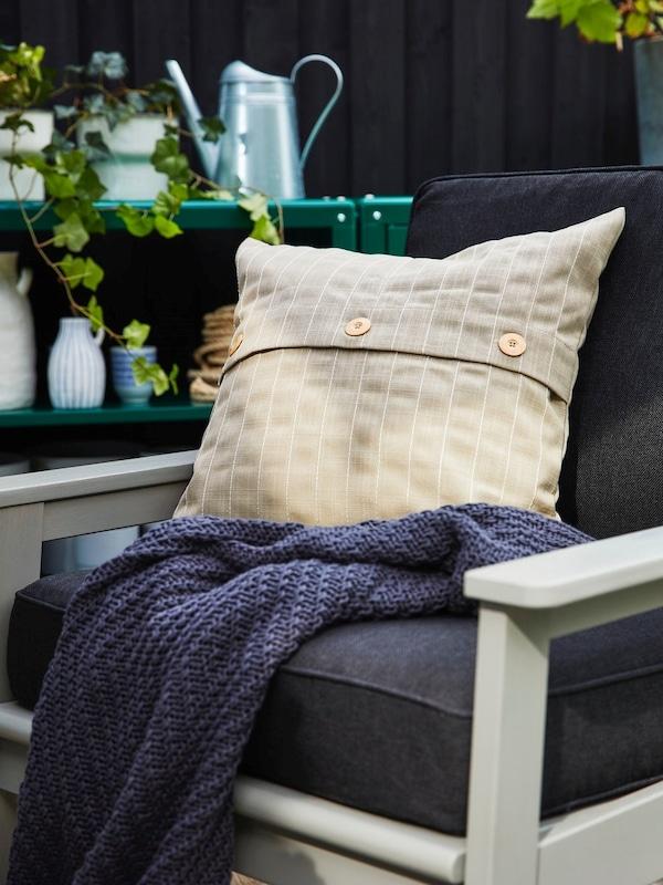 Na fotelu ogrodowym BONDHOLMEN leży granatowy pled i poduszka zewnętrzna FESTHOLMEN.