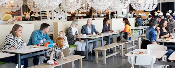 На фото изображены счастливые люди, которые расположились в ресторане и обедают. Здесь есть семьи с детьми, пары, компании друзей - для всех нашлось не только место, но и подходящее блюдо.