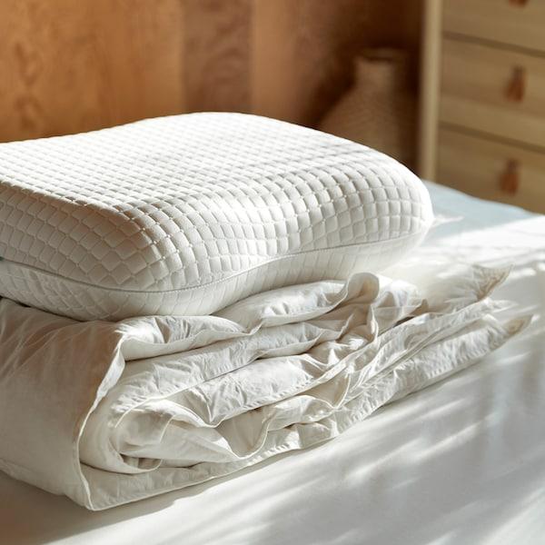 Na neustlanej posteli je kopa posteľných textílií, navrchu je ergonomický vankúš KLUBBSPORRE a v pozadí stojí komoda.