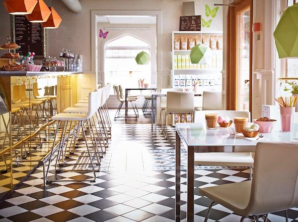 Na obrázku je slnkom zaliata kaviareň s barovým pultom.