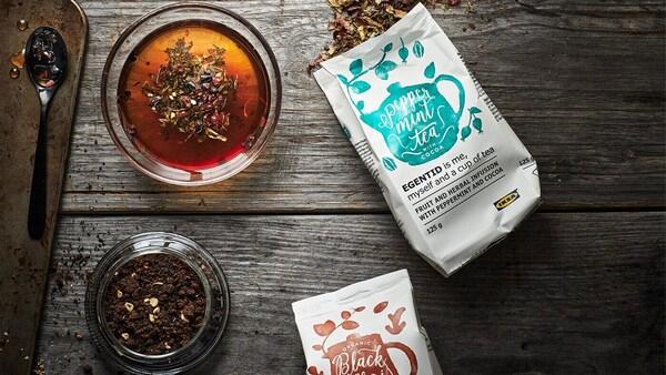 Na obrázku jsou dva balíčky s čaji, které byly vypěstovány udržitelně a šálek čaje.