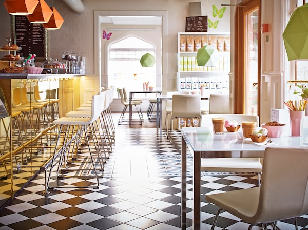 Na obrázku preslnená kaviareň s barovým pultom.