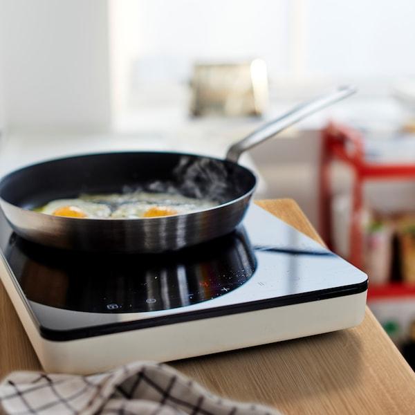 Na panvici IKEA 365+, ktorá stojí na prenosnej indukčnej varnej doske TILLREDA, sa smažia dve vajíčka.