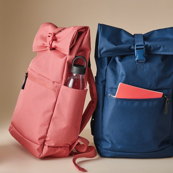Na podlahe je položený oranžovo-červený batoh STARTTID, z ktorého vykukujú školské potreby a desiata.
