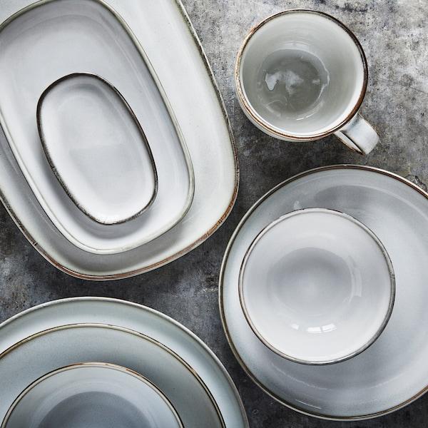 Na šedém povrchu položené světle šedé misky, talíře aservírovací sada ve třech sloupcích se šálkem položeným vedle.