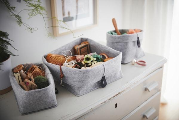 Na staroj, pohabanoj komodi s fiokama nalazi se set RAGGISAR tekstilnih korpi, napunjenih sitnicama i raznim predmetima.