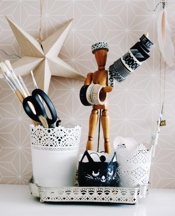На столе коллекция кашпо и инструментов с манекеном.