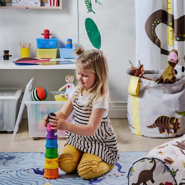Na zemi v dětském pokoji si hraje holčička se stavbnicí, kolem jsou další hračky.