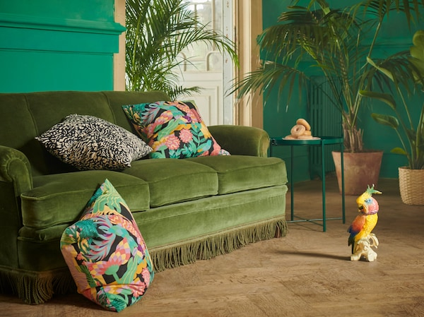 NÄBBFLY and GRIMHILD cushion covers featuring exotic patterns, placed in a green velvet sofa in a grand room with plants.