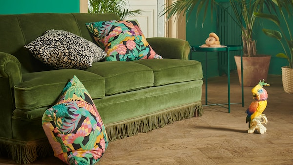 NÄBBFLY and GRIMHILD cushion covers in colourful and exotic patterns on a green velvet sofa in a room with plants.