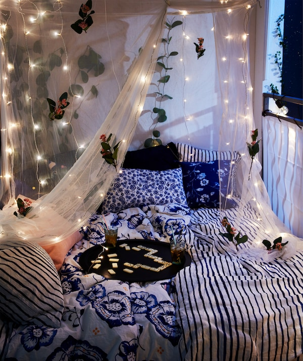 Nächtliche Balkongestaltung mit Doppelbett, darauf ein Tablett mit Getränken. Ebenfalls zu sehen ein Netz, das mit LEDFYR LED-Lichterkette für drinnen in Silberfarben dekoriert ist.