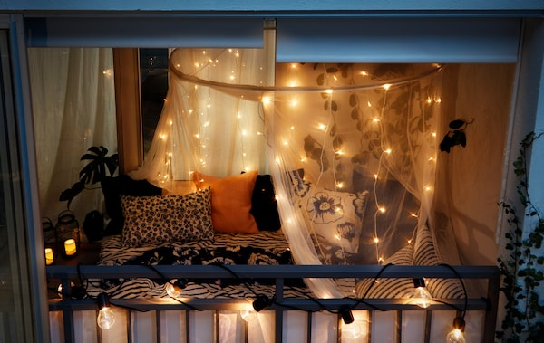 Nächtlicher Blick von draußen auf einen geschlossenen Balkon, dekoriert wie ein Schlafzimmer, u. a. mit SVARTRÅ Lichterketten (12), LED schwarz/für draußen.