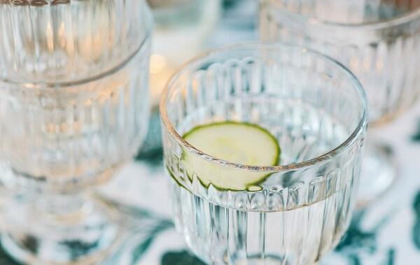 Närbild av transparenta glas fyllda med vatten och en gurkskiva som dekoration.