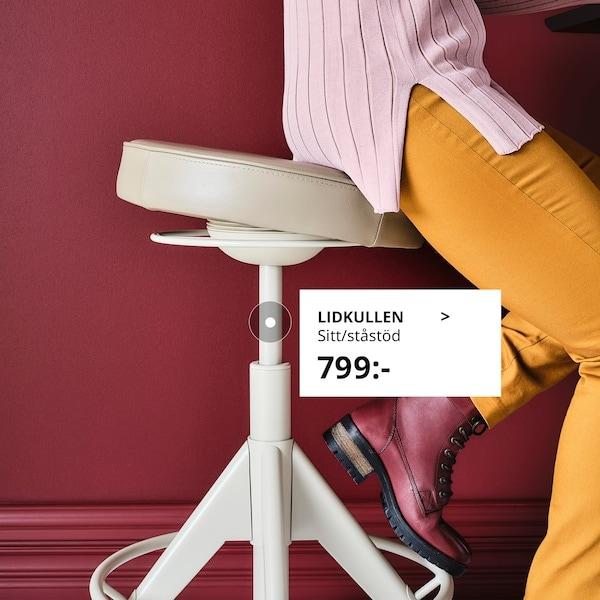 Närbild på en sittande kvinna i färgglada kläder sett didaninfrån på en sittastå stol