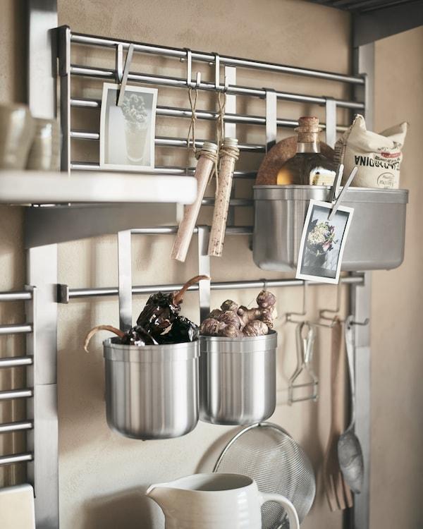 Närbild på KUNGSFORS väggaller i rostfritt stål med magnetiska klämmor, krokar med mindre köksredskap och behållare fyllda med ingefära och andra ingredienser.