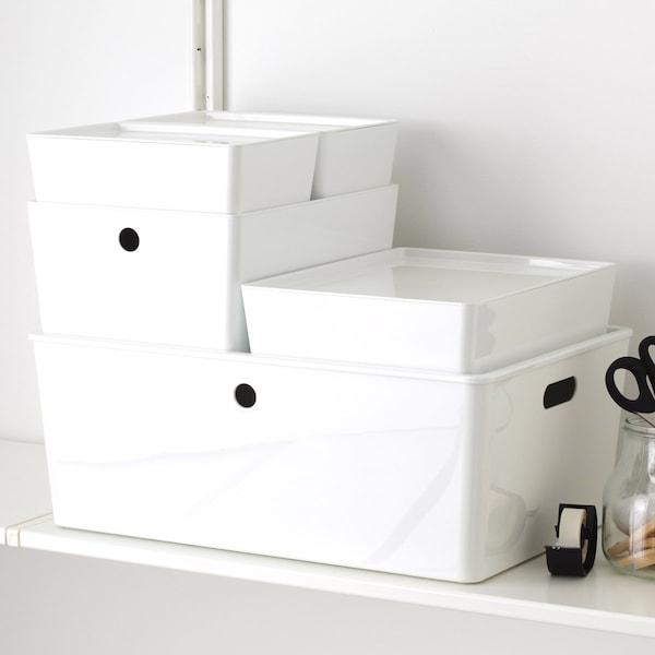 Nærbilde av hvite, resirkulerte plastbokser i forskjellige størrelser, stablet oppå hverandre.