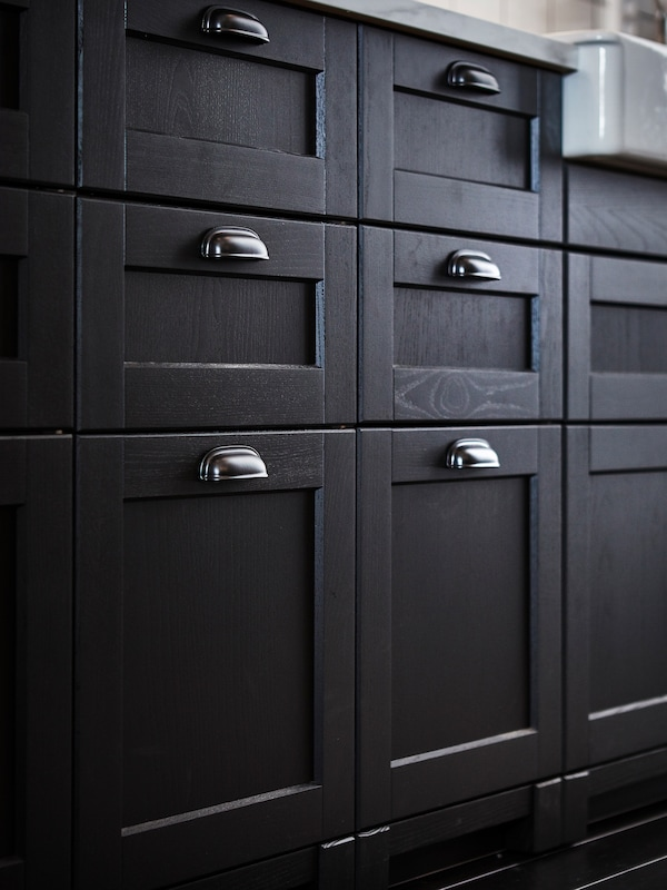 Nærbilde av tradisjonelle, svartbeisede LERHYTTAN skuffefronter med svarte ENERYDA koppehåndtak i et kjøkken.