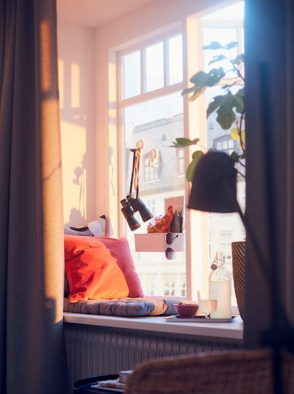 نافذةمضاءةبنورالشمسمع خلفيةللمدينة. توجدوسادة كرسيVIPPÄRT على حافةالنافذة، مع صينيةمن المرطبات، ونبات كبير.