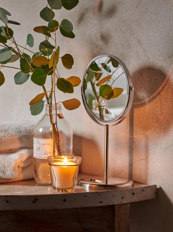 Några handdukar, ett VÄLDOFT ljus och en glasflaska med en kvist eukalyptusblad på en hylla i ett rustikt badrum.
