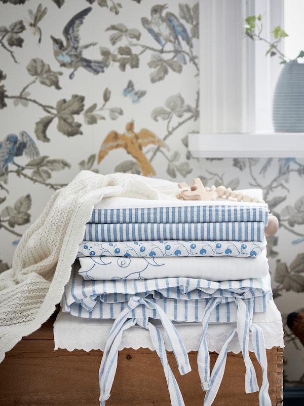 Nahaufnahme der gefalteten IKEA GULSPARV Bettwäsche auf einer Kommode neben einem Fenster