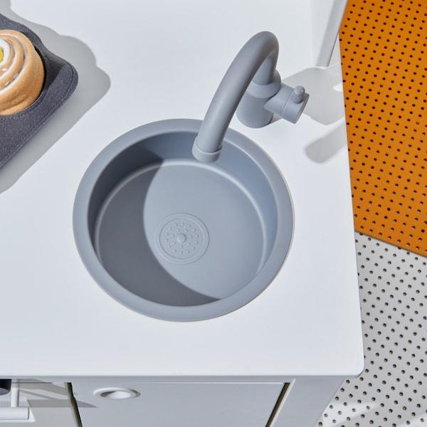 Nahaufnahme der grauen Spüle und und Mischbatterie in SPISIG Spielküche weiß mit Gardinen.