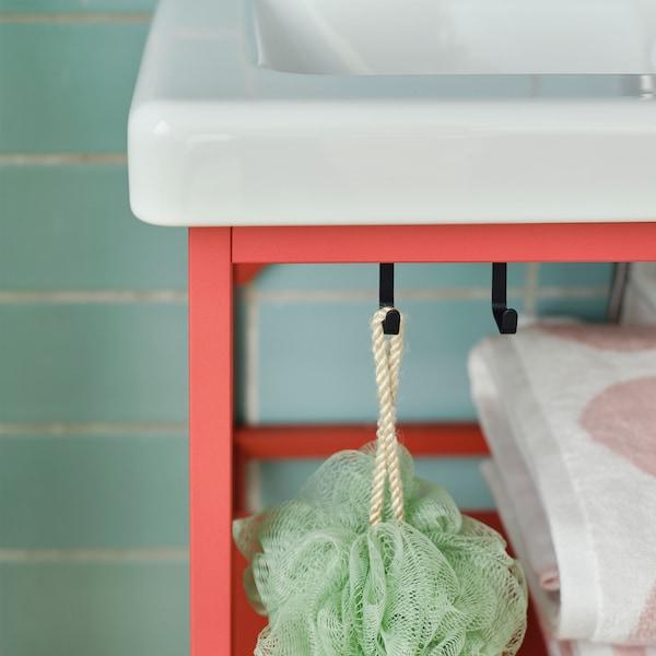 Nahaufnahme der schwarzen Haken an einer ENHET Waschkommode mit ein paar Waschutensilien