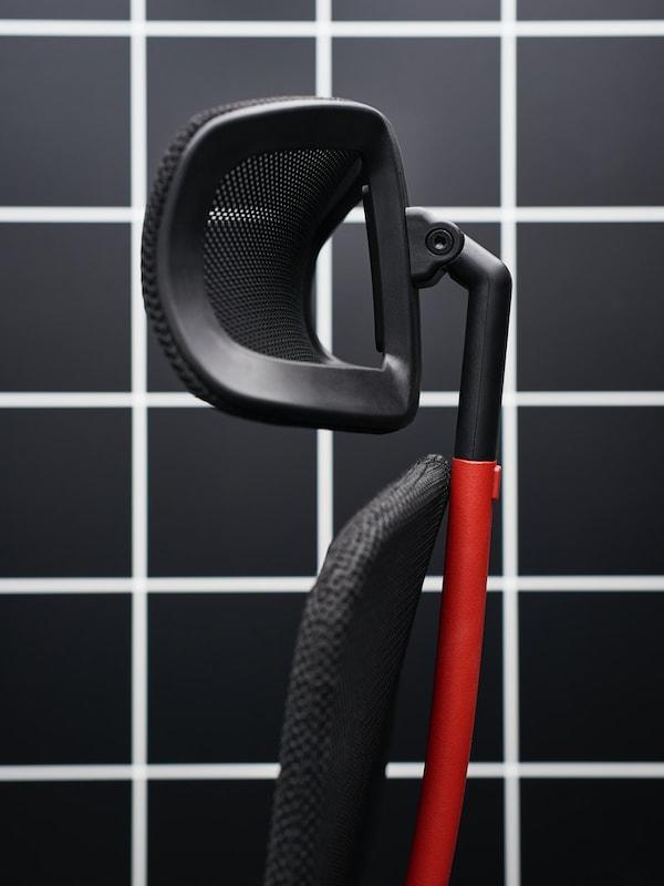 Nahaufnahme der schwarzen Kopfstütze und der schwarzroten Rückenlehne des MATCHSPEL Gamingstuhls vor einem schwarzweißen Karoraster.