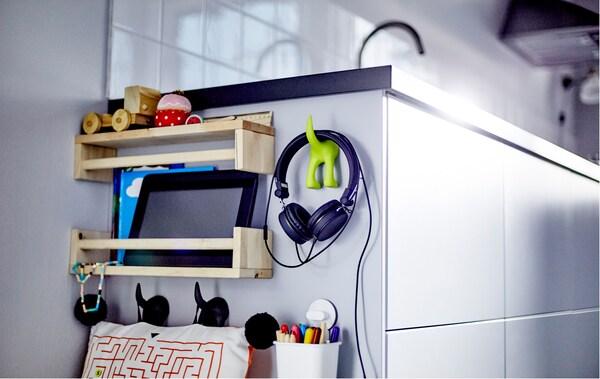 Nahaufnahme der Seite eines Küchenunterschranks mit Holzregalen & Haken, gefüllt mit Spielzeug und Sachen für Kinder.