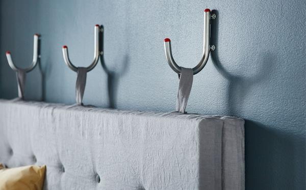 Nahaufnahme einer grauen Sofarückenlehne, die an drei Haken an der Wand befestigt ist