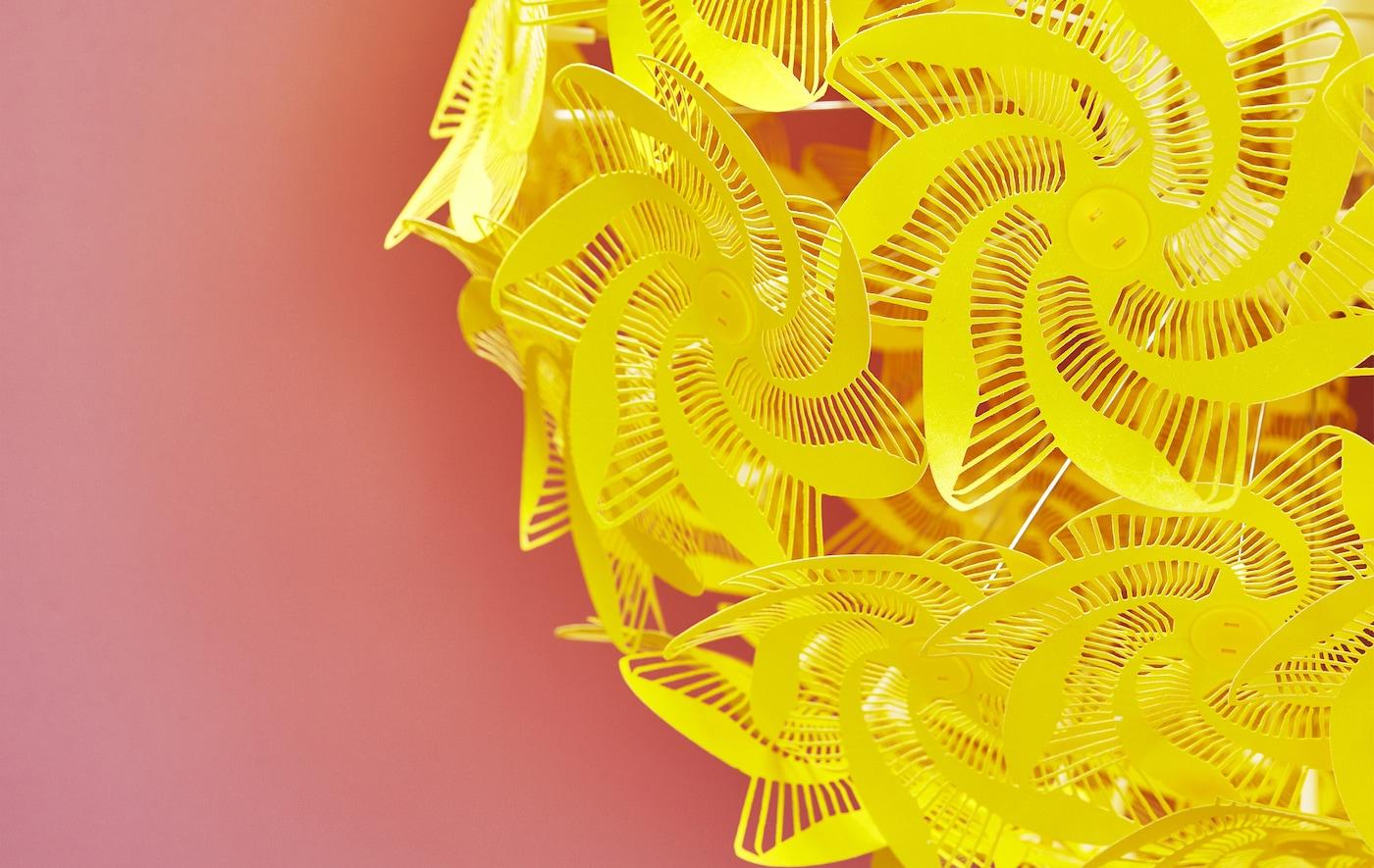 Nahaufnahme einer GRIMSÅS Hängeleuchte in Gelb mit Perforationsmuster vor einem roten Hintergrund