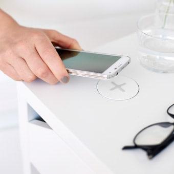 Nahaufnahme einer Hand, die ein Mobiltelefon auf eine kabellose Ladestation legt. Daneben liegt eine Brille.
