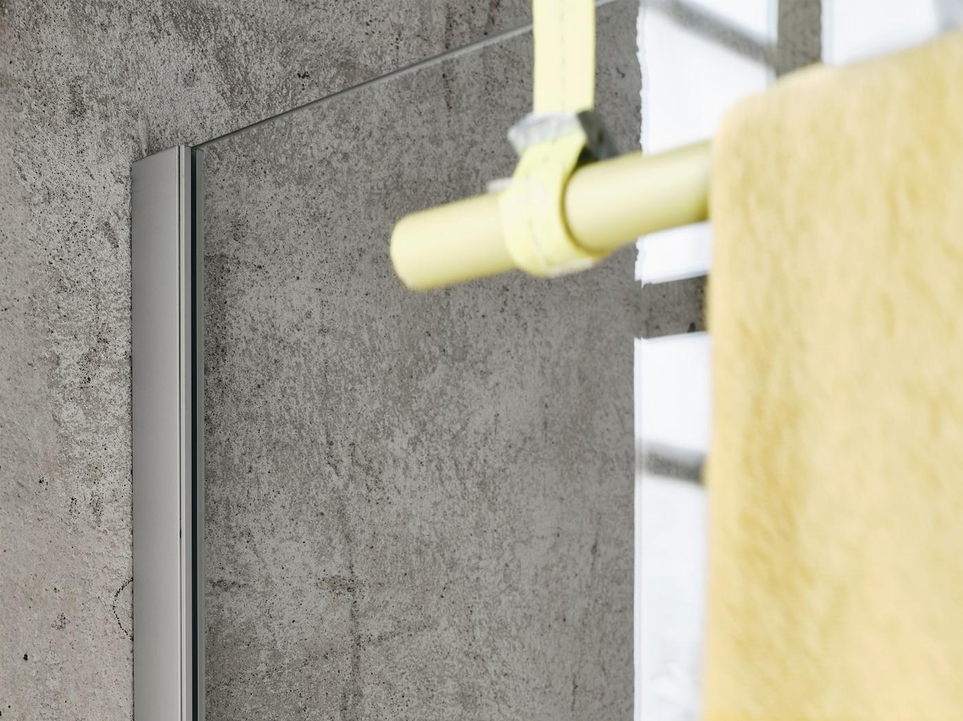 Nahaufnahme einer OPPEJEN Duschwand, die an einer grauen Betonwand befestigt wurde. An ihr hängt eine gelbe Handtuchstange mit einem gelben Handtuch.