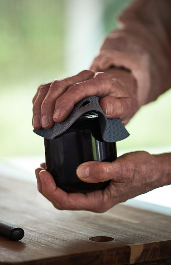Nahaufnahme einer Person, die mit den Händen und mithilfe des OMTÄNKSAM Konservenöffners den Deckel eines Einmachglases öffnet.
