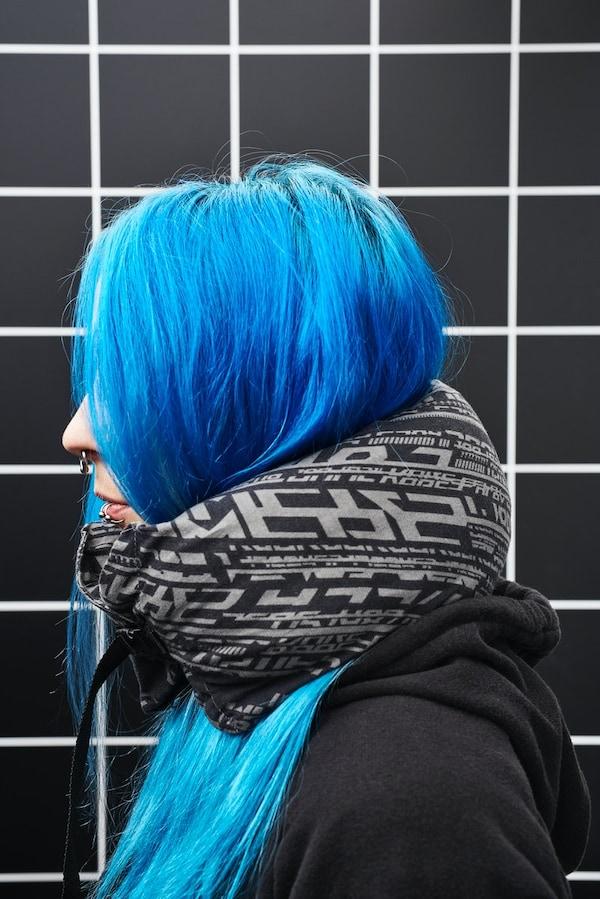 Nahaufnahme einer Person im seitlichen Profil. Sie hat leuchtend blaue Haare und trägt ein schwarzes Hoodie sowie ein LÅNESPELARE Nackenkissen.