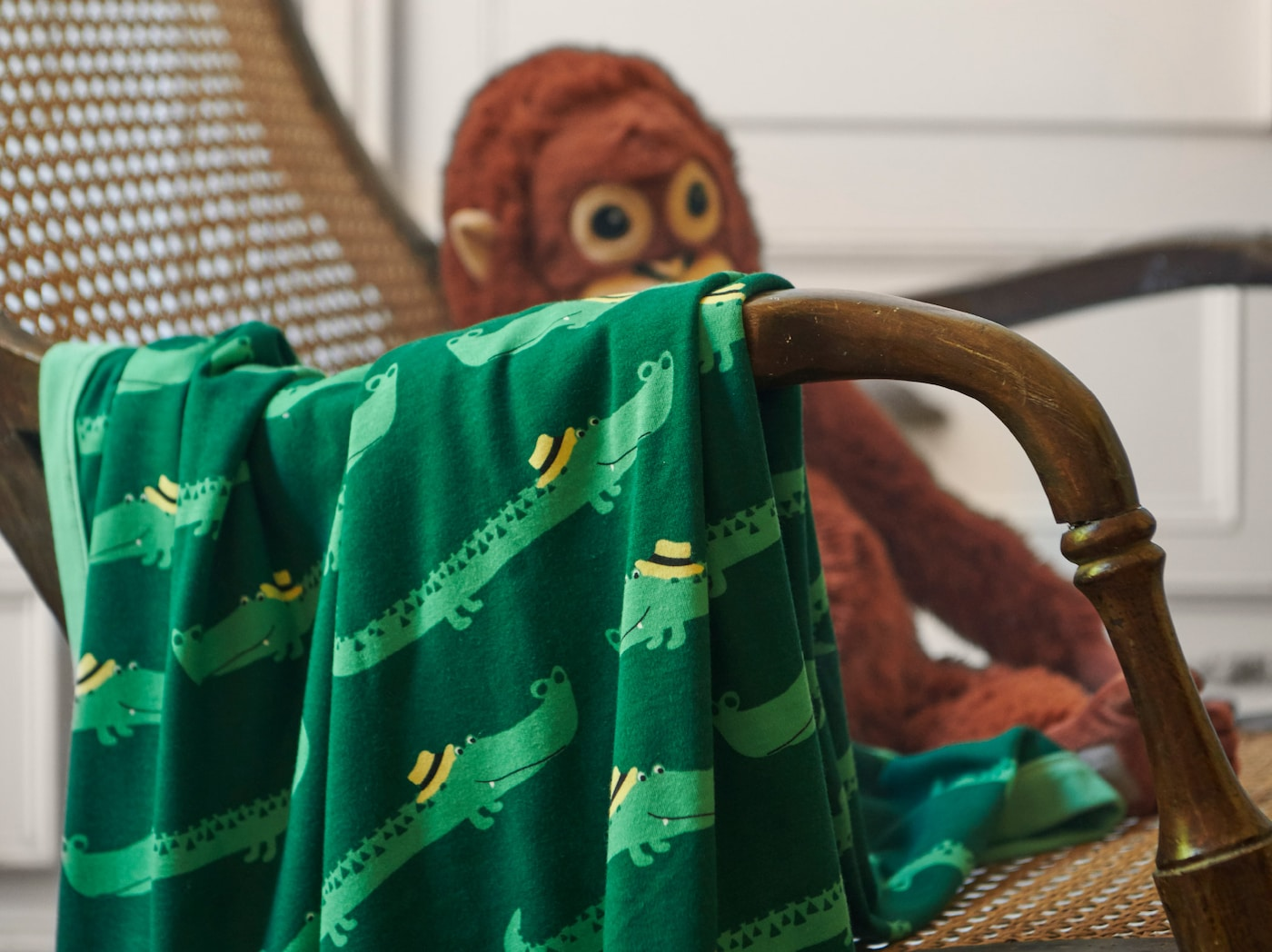 Nahaufnahme einer RÖRANDE Decke mit freundlichen Krokodilen auf grünem Untergrund. Die Decke liegt auf einem Weidenstuhl.