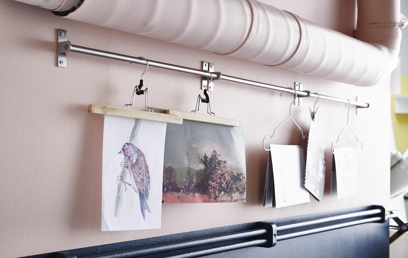 Nahaufnahme einer Stange zwischen zwei Rohren, an denen Kleiderbügel mit Zeichnungen befestigt sind.