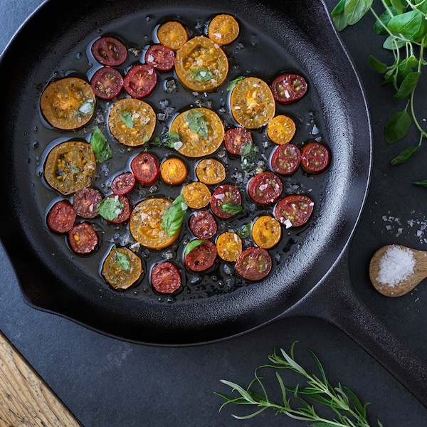 Nahaufnahme einer VARDAGEN-Kohlepfanne mit geschnittenen Tomaten, die auf einem Herd kochen.