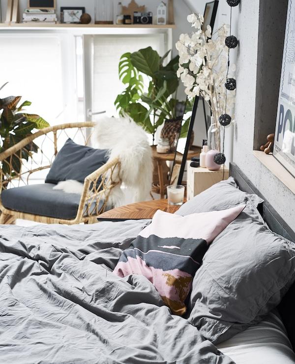Nahaufnahme eines Bettes mit einem Sessel dahinter, u. a. mit ELDTÖREL Kissenbezug rosa/bunt.